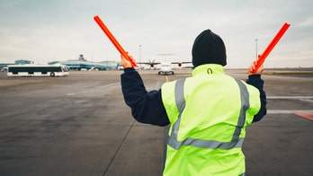 Airline ground crew in Florida holds up signs thanking customers as nearly empty plane prepares to take off