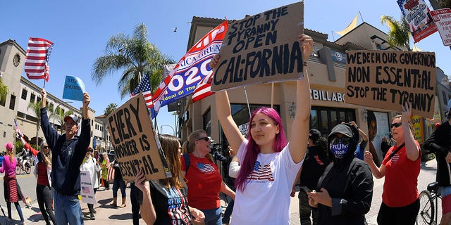 Protestors demonstrate against stay-at-home orders that were put in place due to the COVID-19 outbreak, Friday, April 17, 2020, in Huntington Beach, Calif. (Associated Press)