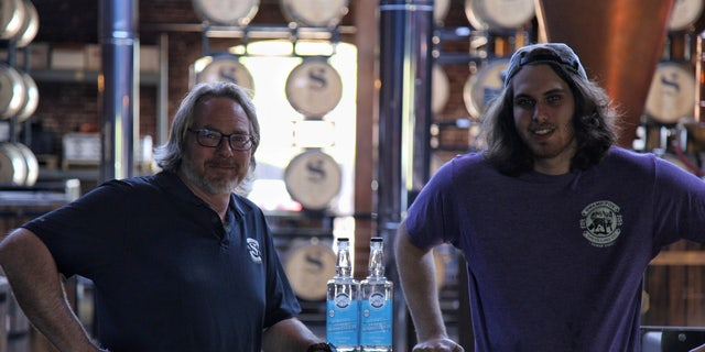 Britt Moon (left), co-owner of Swamp Fox Distilling Co. in Buena Vista, Ga., poses next to a bottle of hand sanitizer made at his distillery (Whisky With A View)