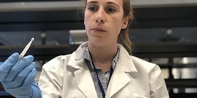 Kaitlyn Sadtler, Ph.D., study lead and principal investigator for laboratory testing, holds up a microsampling device from the home blood collection kit used in the study. (Credit: NIBIB)