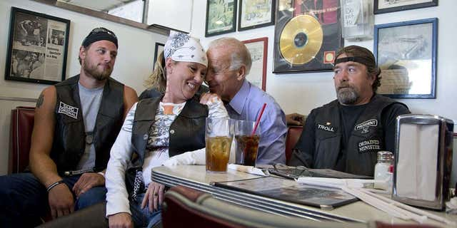 FILE - In this Sept. 9, 2012 file photo, then-Vice President Joe Biden talks to customers, including a woman who pulled up her chair in front of the bench Biden was sitting on, during a stop at Cruisers Diner in Seaman, Ohio. (AP Photo/Carolyn Kaster, File)