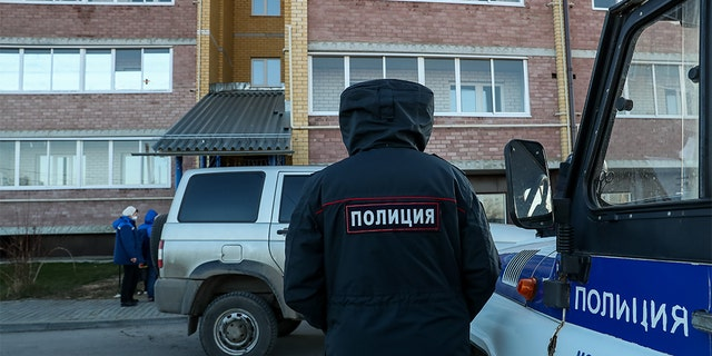 Police at the site of a deadly shooting in an apartment building in the village of Yelatma, Russia.