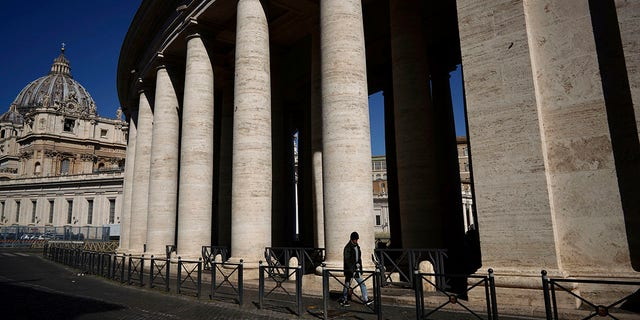 A man walks by Bernini's colonnade in St. Peter's Square during Pope Francis' weekly general audience, streamed by the Vatican television due to restrictions to contain the Covid-19 virus, at the Vatican, Wednesday, April 1, 2020. (Associated Press)