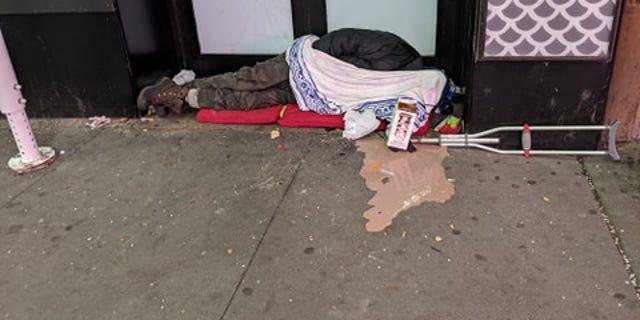 A homeless man across from Penn Station, completely ignored.