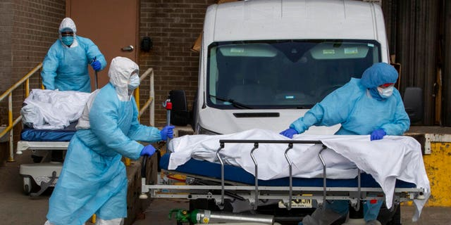 Medical personnel wearing personal protective equipment remove bodies from the Wyckoff Heights Medical Center Thursday, April 2, 2020 in the Brooklyn borough of New York City. (AP Photo/Mary Altaffer)