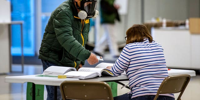 Robert Forrestal, left, wears a full face chemical shield to protect against the spread of coronavirus, as he votes Tuesday, April 7, 2020, at the Janesville Mall in Janesville, Wis. Hundreds of voters in Wisconsin are waiting in line to cast ballots at polling places for the state's presidential primary election, ignoring a stay-at-home order over the coronavirus threat. (Angela Major/The Janesville Gazette via AP)