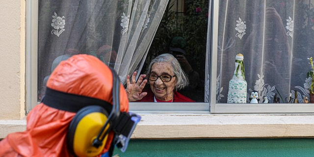 A woman waves to a city worker dressed in a hazmat suit as he disinfects the streets in her neighborhood as a precaution against the spread of the new coronavirus, in Santiago, Chile, Wednesday, April 15, 2020. (AP Photo/Esteban Felix)