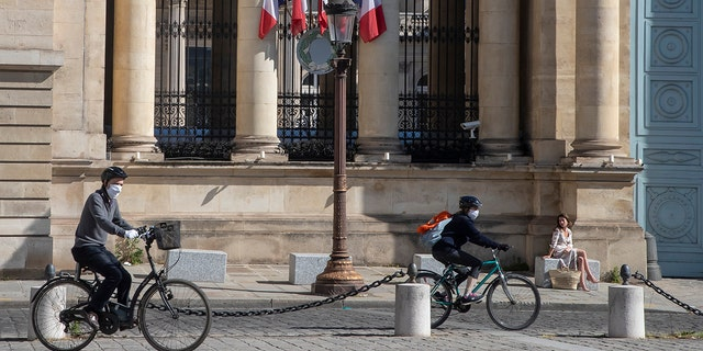 Cyclists wear masks to protect against the spread of the coronavirus ride past a woman who enjoys the sun in front the French parliament in Paris on Sunday. (AP Photo/Michel Euler)