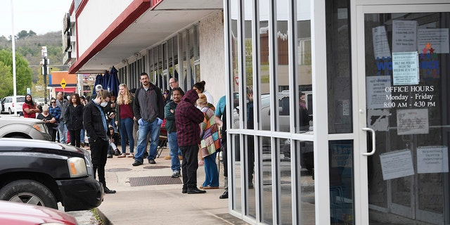 In this Monday, March 30, 2020, photo, a line of around 50 people extends from the door of Arkansas Workforce Center in Fayetteville, Ark. For information about small business loans and applying for Arkansas unemployment benefits go to www.arkansasedc.com/covid19. (JT Wampler/The Northwest Arkansas Democrat-Gazette via AP)