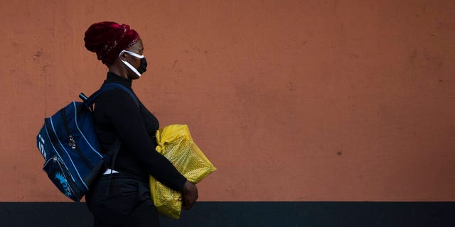 A woman, wearing a protective mask as a precaution against the spread of the new coronavirus, carries her shopping as she walks on the street in Johannesburg, South Africa.