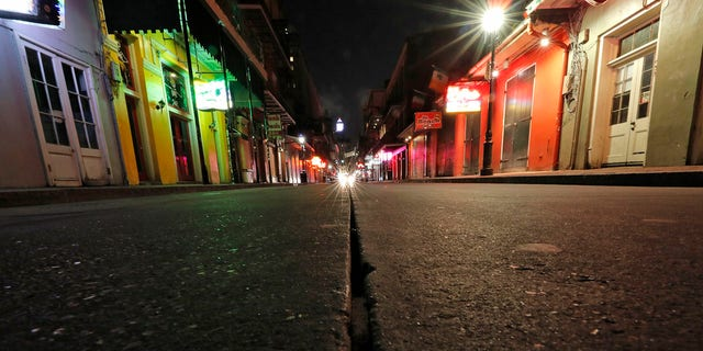 ​​​​​​​A nearly deserted scene on Bourbon Street, which is normally bustling with tourists and revelers, in the French Quarter of New Orleans, March 19, 2020.  (Associated Press)