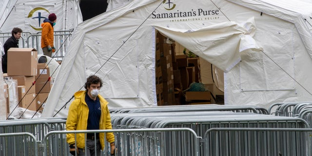 A Samaritan's Purse crew and medical personnel work on preparing to open a 68 bed emergency field hospital specially equipped with a respiratory unit in New York's Central Park on March 31 in New York.  (AP Photo/Mary Altaffer)
