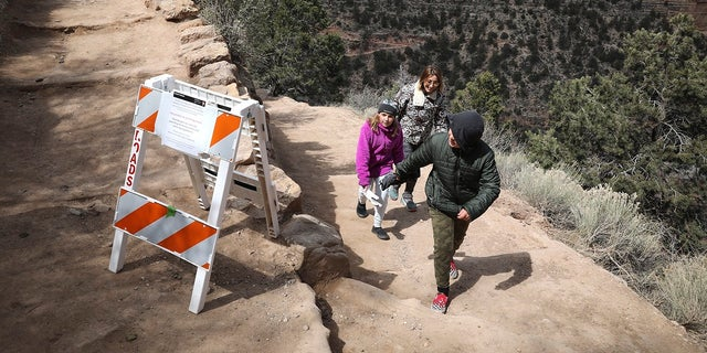 In this March 27, 2020 photo, Shelly Clayton, center, walks up the Bright Angel Trail at Grand Canyon National Park, Ariz., with her children Audrey Kuhar, 11, left, and Cooper Kuhar, 11. (Jake Bacon/Arizona Daily Sun via AP)