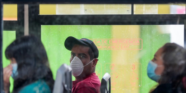 "A bus commuter wears a face mask amid the spread of the new coronavirus in Mexico City, Tuesday, March 31, 2020. Mexico's government has broadened its shutdown of ""non essential activities,"" and prohibited gatherings of more than 50 people as a way to help slow down the spread of the coronavirus. The one-month emergency measures will be in effect from March 30 to April 30."