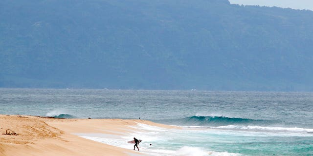A surfer walks out of the ocean on Oahu's North Shore near Haleiwa, Hawaii, Tuesday, March 31, 2020. The state of Hawaii is reporting its first death of an individual who tested positive for the coronavirus.