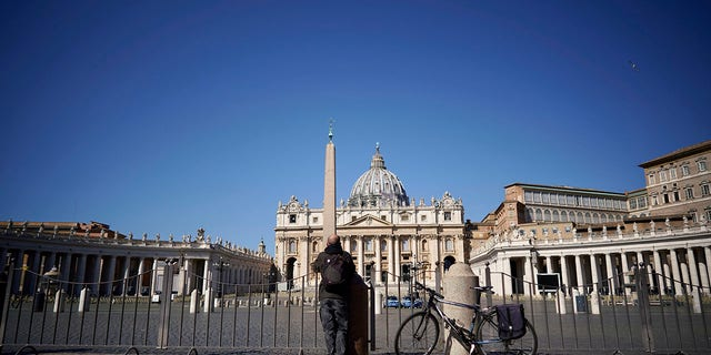 A man stands in front of St. Peter's Square and Basilica during Pope Francis' weekly general audience, streamed by the Vatican television due to restrictions to contain the Covid-19 virus, at the Vatican, Wednesday, April 1, 2020. (Associated Press)