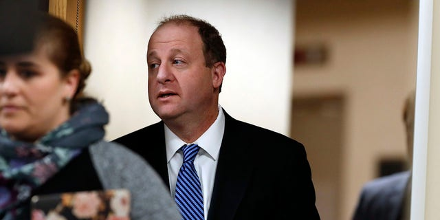 Colorado Gov. Jared Polis enters a news conference in Centennial, Colo., April 1, 2020. (Associated Press)
