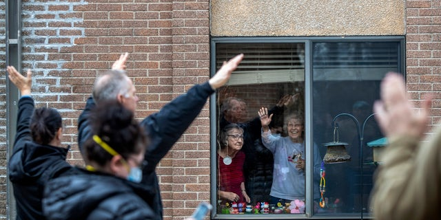 Members of City Impact, a faith-based organization from Cedar Springs, sing and pray for residents and staff at Metron of Cedar Springs nursing home, in Cedar Springs, Mich on April 1. (Cory Morse/The Grand Rapids Press via AP)