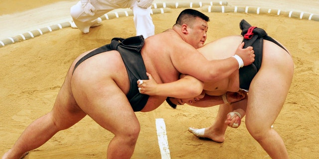 Sumo wrestler Takayuki Ichihara from Japan, left, fights against compatriot Keisho Shimoda in the heavyweight final of the Sumo tournament at the World Games in Duisburg, Germany in 2005. A Japanese sumo wrestler has tested positive for the coronavirus, further threatening postponement of next month's Summer Grand Sumo Tournament which has already been delayed. (AP Photo/Martin Meissner, FIle)