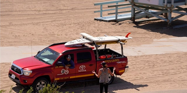 A Los Angeles County Lifeguard speaks to a jogger that was running on closed Playa Del Rey Beach in Los Angeles. Los Angeles County on Friday extended its stay-at-home order through May 15. (AP Photo/Mark J. Terrill)