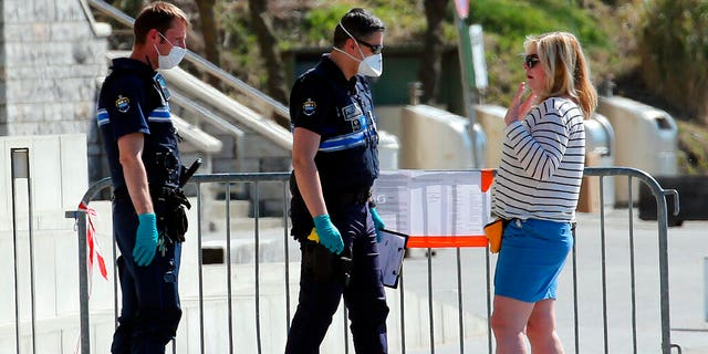 Police officers speak to a woman during a nationwide confinement to prevent the spread of the coronavirus, in Biarritz, France, Saturday April 4, 2020. The new coronavirus causes mild or moderate symptoms for most people, but for some, especially older adults and people with existing health problems, it can cause more severe illness or death. (AP Photo/Bob Edme)