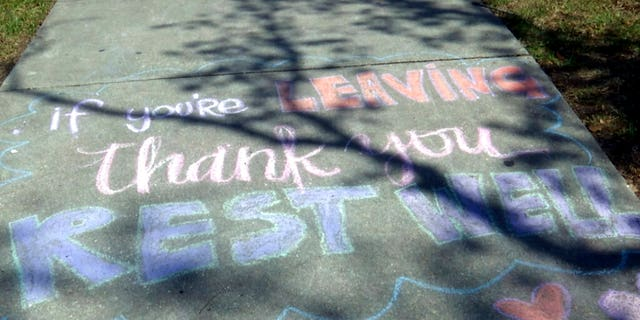 "A message written in chalk that reads, ""If you're leaving, thank you, rest well,"" on a sidewalk at Ochsner Medical Center in New Orleans. (AP Photo/Stacey Plaisance)"