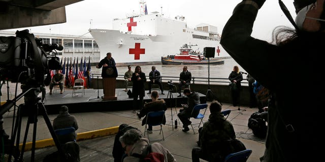 A journalist records speakers at a press conference following the arrival of USNS Comfort, a 1,000-bed marine hospital ship, March 30, 2020, at Pier 90 in New York. The vessel will be used to treat patients who do not have the new coronavirus as land-based hospitals are filling up to capacity with those who do.