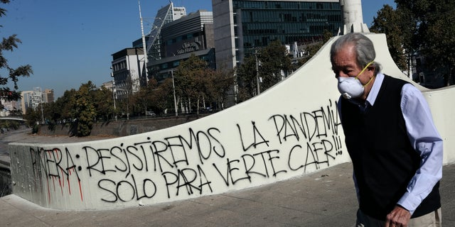 """A man wearing a face mask walks past graffiti against Chilean President Sebastian Piñera that reads in Spanish """"Piñera, we will resist the pandemic just to see you fall!,"""" amid the spread of the new coronavirus in Santiago, Chile, Monday, April 6, 2020. (AP Photo/Esteban Felix)"""