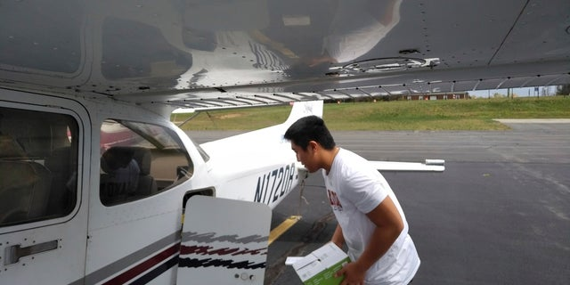 In this photo provided by Thomas Kim, TJ Kim, 16, loads medical supplies into a plane in Leesburg, Va., before flying to a hospital in Luray. Kim began delivering donated medical supplies to rural hospitals in need after realizing his flight training could be put to good use during the coronavirus pandemic. (Thomas Kim via AP)