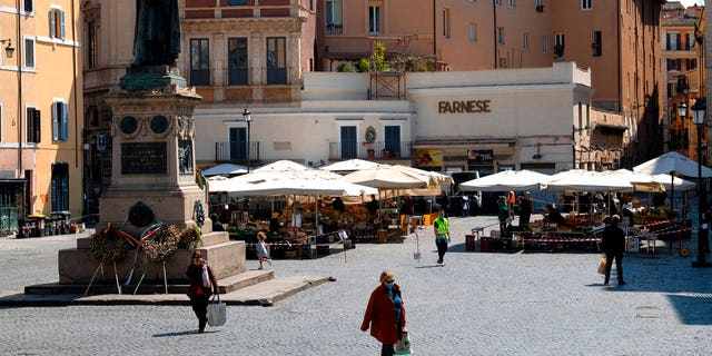 People shopping at Campo de Fiori fresh fruits and vegetables open market, as the statue of Giordano Bruno watches over the square, in Rome, Tuesday, April 7, 2020.