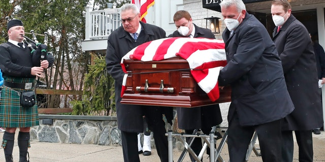The casket of veteran Mary Foley is carried out of a funeral home, Wednesday, April 8, 2020, in Arlington, Mass. Foley, who died at the age of 93, served in the U.S. Air Force, including WWII. Due to the coronavirus crisis, she cannot be given a formal military funeral. (AP Photo/Elise Amendola)
