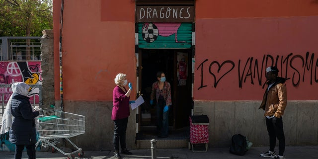 """Volunteers, wearing face masks and gloves, distribute food bags at the """"Dragones de Lavapies"""" soccer association in Madrid, Spain, Wednesday. Amid the coronavirus lockdown, volunteers meet at the soccer youth club to distribute food to hundreds of families at risk of social exclusion. (AP Photo/Bernat Armangue)"""