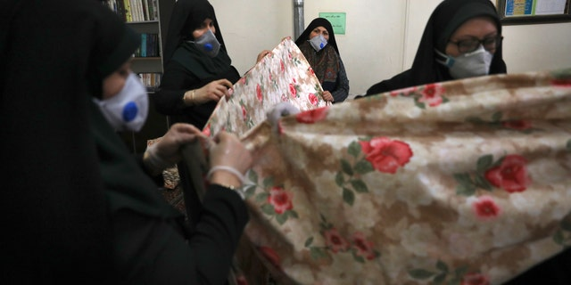 """Volunteer women wearing face masks to curb the spread of the new coronavirus prepare fabric to sew bed sheets for hospitals, at a mosque in Tehran, Iran this month. A human rights organization says thata jailed Iranian Instagram star— known for her transformation into a """"zombie Angelina Jolie"""" — is currently on a ventilator after contracting the coronavirus in custody. (AP Photo/Vahid Salemi, File)"""