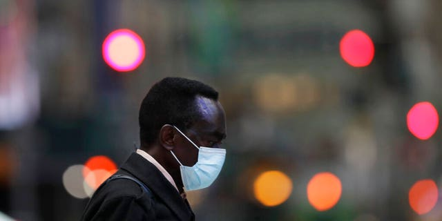 A man wearing a mask walks through New York's Times Square, Thursday, April 9, 2020, during the coronavirus epidemic. (AP Photo/Mark Lennihan)
