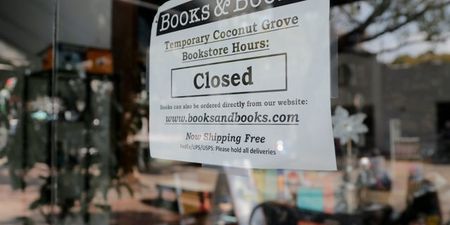 A sign on locally owned business Books & Books says the store is closed during the coronavirus pandemic, Thursday, April 9, 2020, in Miami. With 6.6 million people seeking unemployment benefits last week, the United States has reached a grim landmark: roughly one in 10 workers have lost their jobs in just the past three weeks to the coronavirus outbreak. (AP Photo/Lynne Sladky)