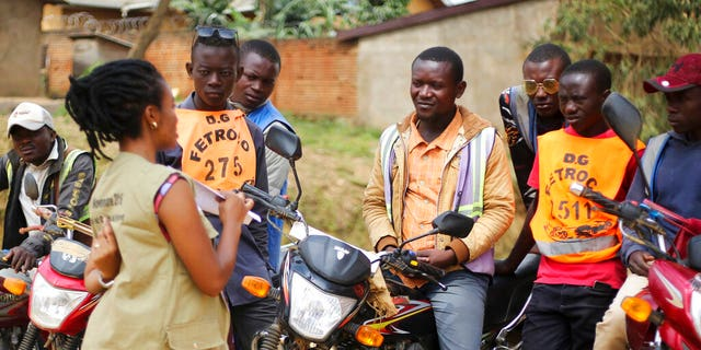Martine Milonde, left, a Congolese community mobilizer who works with the aid group World Vision in Beni, eastern Congo, which became the epicenter of the Ebola outbreak, engages the public about coronavirus prevention.