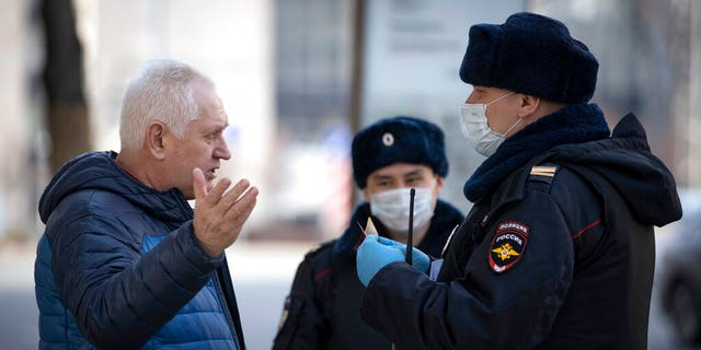 Russian police officers, wearing face masks to protect from coronavirus, check documents of a man to ensure a self-isolation regime due to coronavirus, in Moscow, Russia.