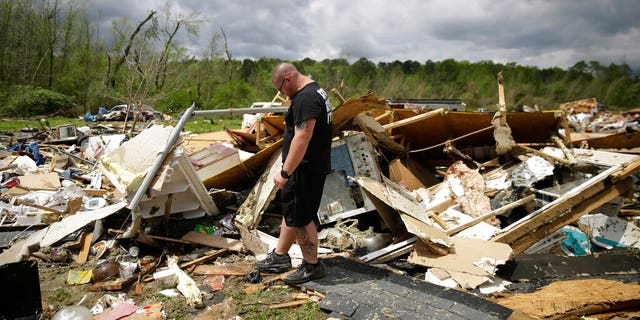Aaron Pais kicking around debris at a mobile-home park wrecked by a tornado in Chatsworth, Georgia.