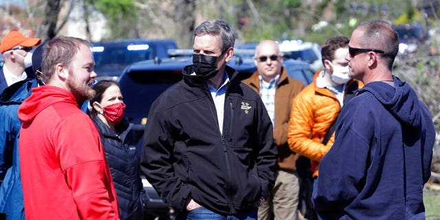 Tennessee Gov. Bill Lee, center, talks with residents as he visits a storm-damaged area Tuesday, April 14, 2020, in Chattanooga, Tenn.