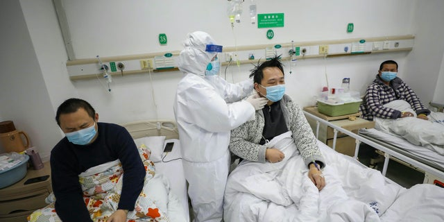 A doctor checks the condition of a patient at Jinyintan Hospital, designated for critical COVID-19 patients, in Wuhan in central China's Hubei province.  (Chinatopix Via AP)