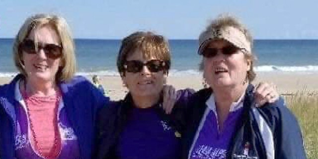 In this Sept. 2018 photo, Joanne Mellady, right, poses with her sisters Jean Sinofsky, left, and Joyce Smith, center, at a Massachusetts beach on Cape Cod during a bike trek fundraiser for Alpha 1.org. Mellady, who received a double lung transplant in 2007, died of the coronavirus in March 2020.