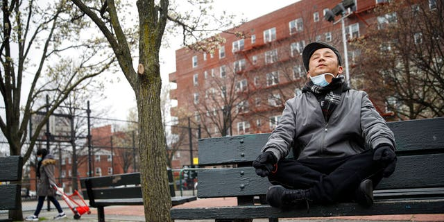 Lobsang Tseten meditates and practices breathing exercises alone to maintain social distancing at a playground in New York.