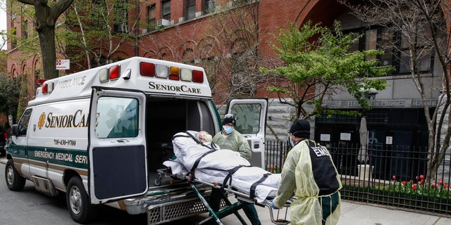 A patient is loaded into the back of an ambulance by emergency medical workers outside Cobble Hill Health Center, Friday, April 17, 2020, in the Brooklyn borough of New York.
