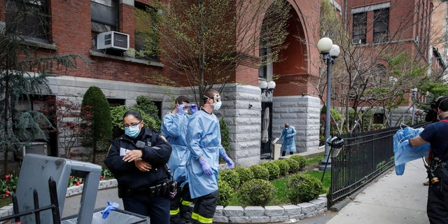 NYPD officers, FDNY firefighters, and emergency workers begin to discard and disrobe from their protective equipment after an emergency call at Cobble Hill Health Center Friday in the Brooklyn borough of New York. (AP Photo/John Minchillo)