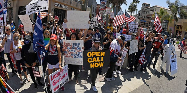 Protesters demonstrate against stay-at-home orders that were put in place due to the COVID-19 outbreak, Friday, April 17, 2020, in Huntington Beach, Calif. (Associated Press)