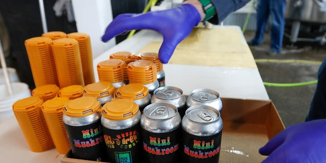 A worker puts four-pack covers on canned beers after they came off the filling conveyor at the ShuBrew craft brewery in Harmony, Pa on April 16. After the state liquor control board closed the Pennsylvania state-owned stores that retail nearly all of the state's liquor in March, the small microbrewery business pulled an all-nighter to retool its website and operations and went to online ordering and curbside pickup for patrons at their Zelienople, Pa. restaurant. (AP Photo/Keith Srakocic)