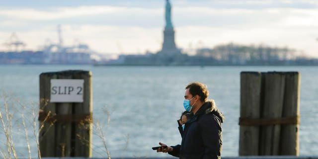 Pedestrians wearing face masks while walking in Battery Park on Saturday in New York City. (AP Photo/Frank Franklin II)