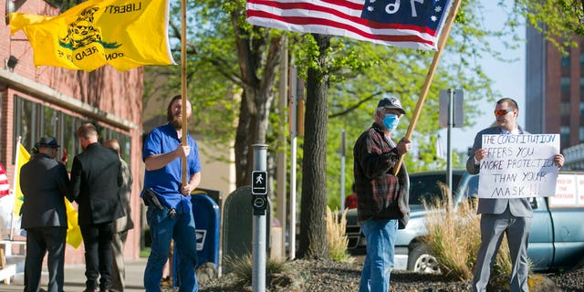 Kenton Gartrell, Patrick Ray and Garth McKinney, from left, attend a rally to protest the Yakima City Council's decision to formally censure Councilman Jason White, Tuesday, April 21, 2020, outside City Hall in Yakima, Wash.