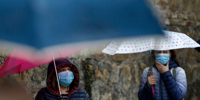 People line up during a free distribution of protective masks against COVID-19 by volunteers of the Chinese Evangelical Christian Church, in Rome, Wednesday, April 22, 2020. (Cecilia Fabiano/LaPresse via AP)