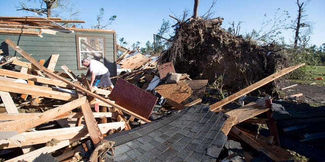 David Maynard sifts through the rubble searching for his wallet, Thursday, April 23, 2020 in Onalaska, Texas, after a tornado destroyed his home the night before. Maynard was inside his home when a tornado devastated the area.